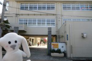 「防災訓練」の会場、小浜小学校の校門前にやってきたまちキョン。校門を背にポーズをとるまちキョンが写っています。