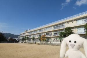 防災訓練が終わった会場(小浜小学校)を後にしようとするまちキョン。その背後に、広い運動場と校舎と、澄み渡った青空が写っています。