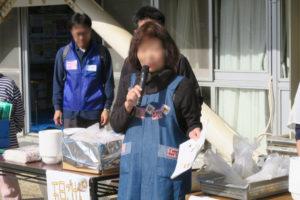 炊き出し訓練用に準備された机の前で、紺色のエプロンを着てマイクを手にした女性が、訓練の説明している様子が写っています。