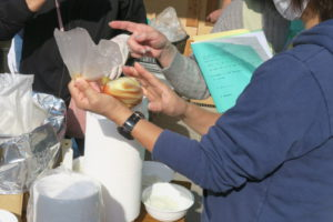 湯煎調理のパック作りを体験。説明を聞きながら、耐熱のポリ袋を片手に持ち、一食分の食材を入れようとしているところが写っています。