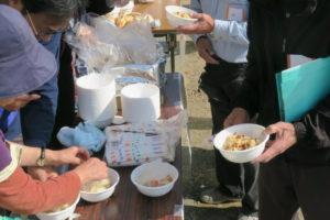 パッククッキングの様子です。テーブルの上に紙皿が積まれており、その横に袋いっぱいの割りばしも見えます。向かって左側の女性は、今出来上がったばかりの食材を盛り付けようとしています。その右側には、肉じゃがの入ったお皿が置かれています。その右側には、黒っぽい服の人が五目ごはんの入ったお皿を両手に持っています。わいわいがやがやの雰囲気が伝わってきます。