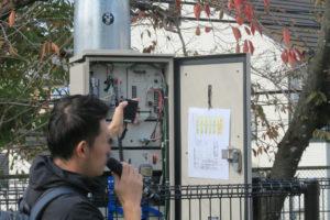 防災スピーカーのテスト放送の様子。宝塚市総合防災課の職員さんが、公園内に防災用に設置された器具の中を開けて使い方の説明をしています。