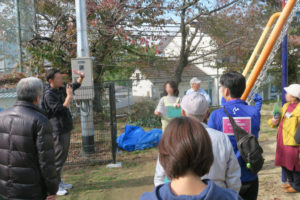 公園内で、宝塚市総合防災課の職員さんが防災スピーカーについて説明するのを、遠巻きに囲んで聞いているみんなの様子が写っています。
