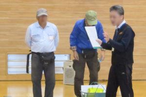 小学校のアリーナ(体育館)で、避難所開設の訓練の様子。説明をする男性スタッフと、その説明を聞く2人の年配の男性が写っています。