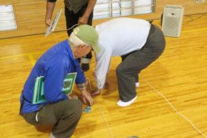 小学校のアリーナ(体育館)で、避難所開設の訓練の様子。避難スペースや通路、車椅子対応などを考えて、2人の男性が実際に床の上に目印をつけているところが写っています。