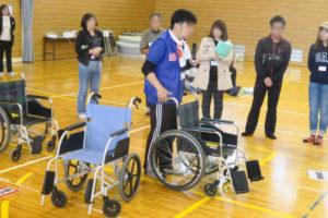 小学校のアリーナ(体育館)で、避難所開設の訓練の様子。宝塚市健康福祉サービス公社の方が車椅子の説明をしているところです。車椅子が3台写っていて、その1つを実際に押しながら説明をし、それを取り囲むようにして説明を聞いている地域のみなさんが写っています。