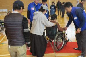 小学校のアリーナ(体育館)で、宝塚市健康福祉サービス公社の方から、車椅子の使い方などの説明を受け、車椅子の体験をしているところです。車椅子に年配の女性が座り、それを若い女性が押してみている様子が写っています。