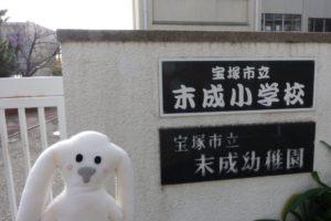 末成小学校の校門の前でまちキョンが記念撮影している様子。