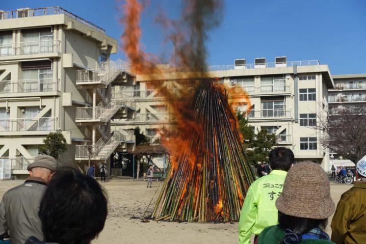 末成小学校の校庭でやぐらが大きく燃える様子。それを眺める人たち。