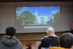 ホワイトボードに、小林聖心女子学院の白い校舎が映し出されています。