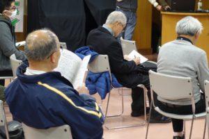 3~4人の参加者が説明を聞いたり、資料に熱心に書き込みを入れてりする様子の後ろ姿が写っています。