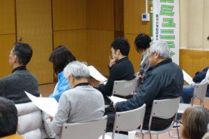 7~8名の参加者が資料を見ながら説明を聞いている様子を少し斜め後ろから撮った写真です。