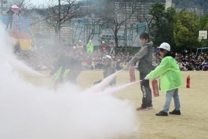 校庭でおこなわれた防災訓練で。消火器を使って火を消す様子とそれを見ている児童たち。