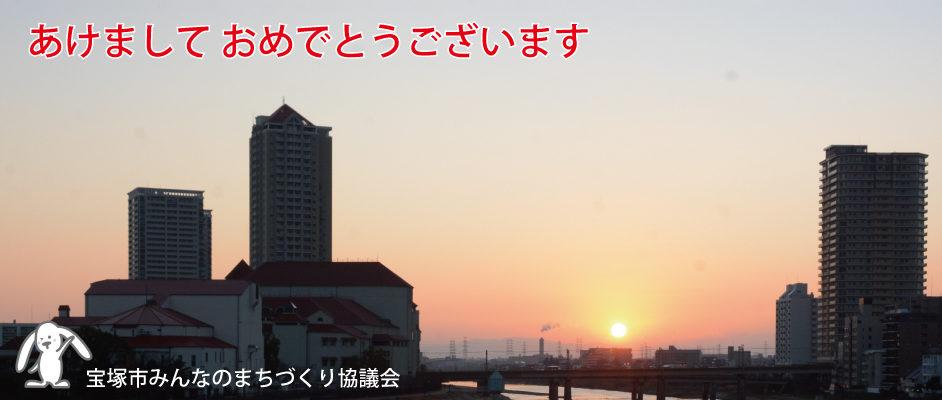宝来橋から南向き、初日の出が登って空が赤く色付いている。左手には宝塚大劇場、右手には高層マンションが見える