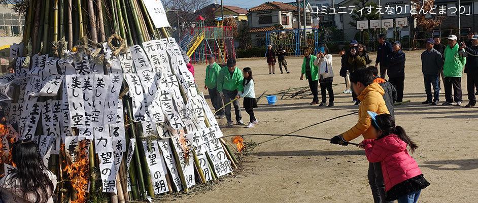 コミュニティすえなりで行われたとんどまつりの様子。末成小学校の校庭にたくさんの竹が組まれて、書き初めが周りに巻かれている。そこに子供達が一本の竹を持って離れた位置から火をつけ始めているところ。周りには地域の方が集まって見守っている。
