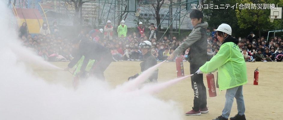宝小コミュニティで行われた合同防災訓練の様子。校庭で、手前の2人が消火器を噴射している。後方にはその様子を見ている子供達がたくさんいる。