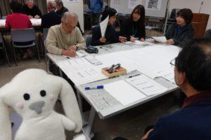 長机を並べて正方形の「シマ」を作り、それを囲むように何人かがグループになって座っています。その左横にまちキョンが立っています。