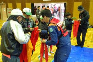 体育館の中で、参加者の皆さんがそれぞれ赤い三角巾を手に持ち、結び方などの使い方を教えてもらっています。