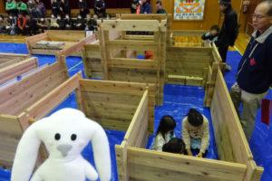 災害用ログモジュールを迷路のように組み立てて、その中の1つのスペースに数人の子どもたちが集まっています。そのスペースの外側にまちキョンが立っています。