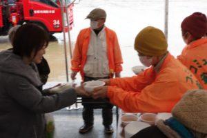 オレンジ色のジャンバーを着たスタッフの人から、炊き出しの豚汁を受け取る参加者の人が写っています。