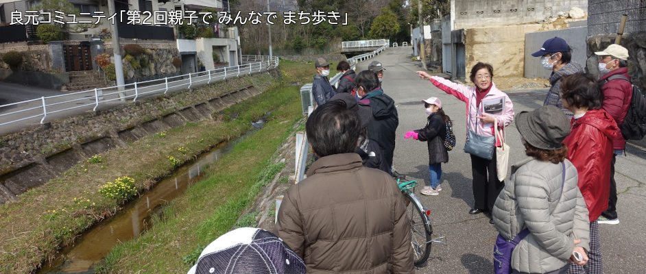 良元コミュニティの「第2回親子でみんなでまち歩き」の様子。10名以上の方が小仁川を左手に見つつ、ガイドの方から説明を聞いている。