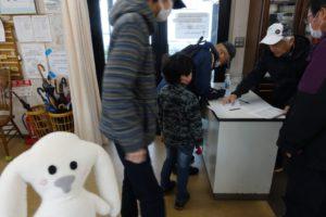 「第2回 親子で みんなで まち歩き」の受付がある塔の町会館に到着し、受付の前で順番を待つ親子の近くに立つまちキョンです。