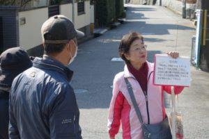 まちの中で、ガイドの女性(古村さん)が説明の紙を左手に持ち、参加者に説明する様子が写っています。向かって左側に説明を聞く背の高い男性と、少し小柄な女性の後ろ姿が写っています。