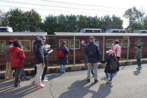 まち歩きがいよいよスタート。阪急電車今津線沿いをみんなで歩いている様子が写っています。