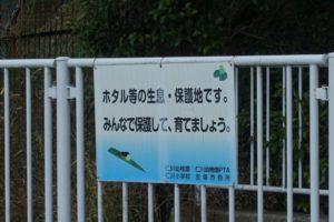 白い柵にかけられた白い看板が写っています。看板には「ホタル等の生息・保護地区です。みんなで保護して育てましょう」と書かれています。