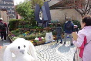まち歩きの途中で通りかかった花壇です。右側にガイドの女性(古村さん)、左側にまちキョンが写っています。