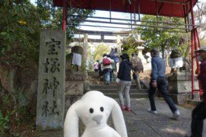 まち歩きの折り返し地点、石に「宝塚神社」と書かれた 門標を背に立つまちキョンが写っています。遠くに鳥居が見え、その鳥居に続く石段を参加者たちが歩いています。
