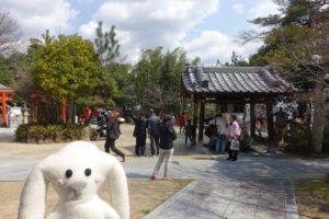 宝塚神社の境内に入ったまちキョン。まちキョンの後ろに広い境内と石畳の参道が写っています。向かって右奥に手水舎が見えます。手水舎の周辺には人が集まっています。