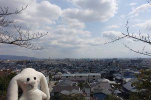 宝塚神社の境内から見下ろす宝塚の街並み。その向こうに白い雲が浮かぶ青い空が続いています。左側にまちキョンがちょこんと写っています。