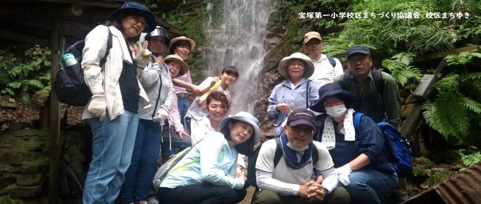 宝塚第一小学校区まちづくり協議会ブログ「校区まち歩き」から。滝を背景に、男女合わせて12人がポーズをとって写真に写っている