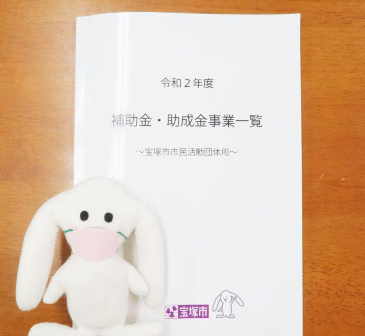 冊子「令和2年度補助金・助成金事業一覧~宝塚市市民活動団体用~」がテーブルに置かれ、その前にマスクをしたまちキョンが映っている