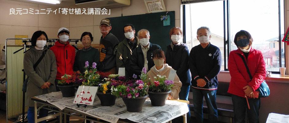 良元コミュニティの寄せ植え講習会での集合写真。10人の男女が映っており、手前のテーブルには6鉢前後の寄せ植えの鉢が載っている