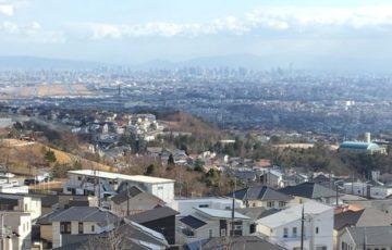 山手台の高台から見下ろした風景で、右側には学校、左側には空港など、眼下に街の風景が広がっている。