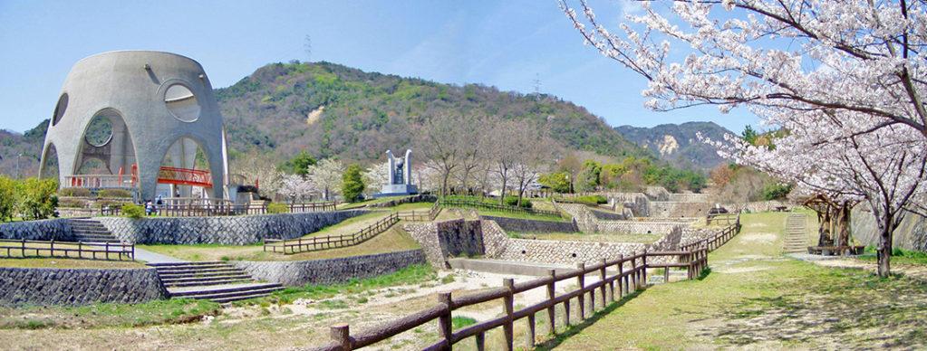 川の対岸の右側に鎮魂の碑、左側に砂防のモニュメントが見える。遠方には山並みと青空。右手には桜が咲いている。